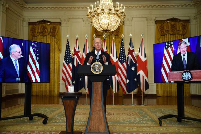 De Amerikaanse president Joe Biden tijdens zijn virtuele persconferentie met de Britse premier Boris Johnson (rechts) en de Australische eerste minister Scott Morrison (links).