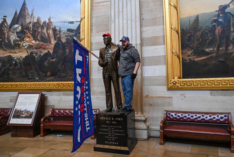 Een relschopper beklimt een standbeeld van president Ford. Beeld AFP