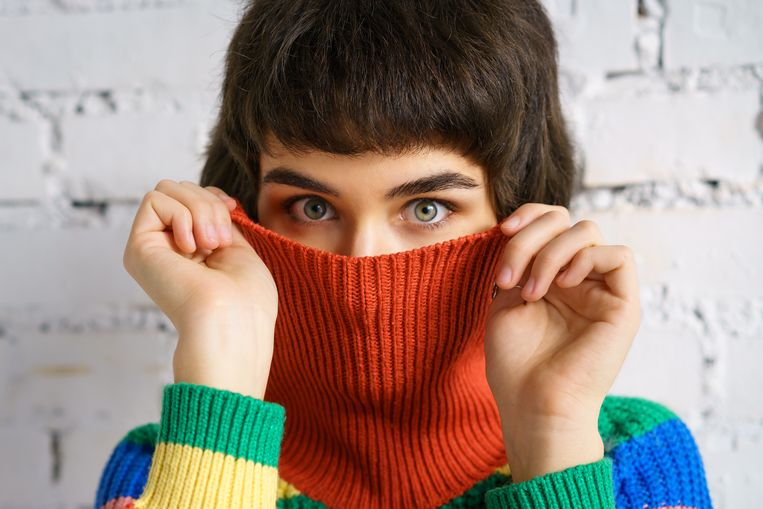 Portrait of a young woman in a multicolored sweater, covering her face with a sweater . The concept of shyness Beeld Getty Images/iStockphoto