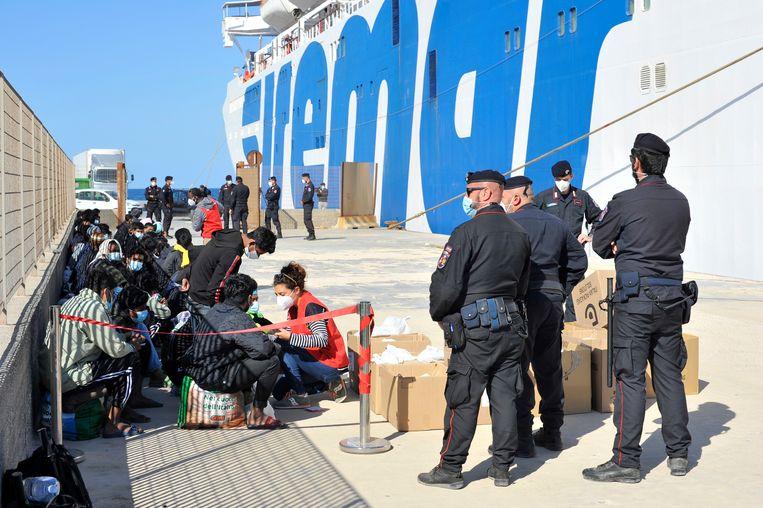 Onder toezicht van Italiaanse politieagenten wachten minderjarige migranten donderdag op vertrek van de veerboot van Lampedusa.  Beeld /Salvatore Cavalli / AP