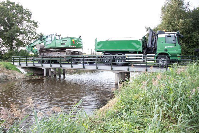 Wethouder Nico Lansink Rotgerink opent de brug over de Radewijkerbeek door er met een zwaar beladen oplegger overheen te rijden.