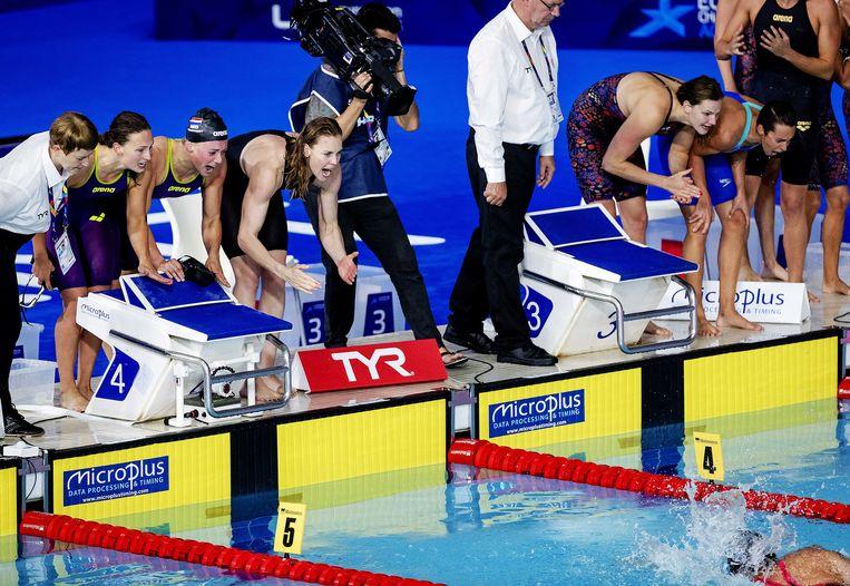 De Nederlandse ploeg (l) schreeuwt de longen uit het lijf, maar slotzwemster Ranomi Kromowidjojo komt een fractie tekort. Beeld ANP