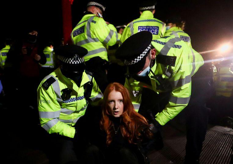 Een vrouw wordt gearresteerd tijdens de wake ter ere van de vermoorde Sarah Everard in de Londense wijk Clapham. Beeld REUTERS
