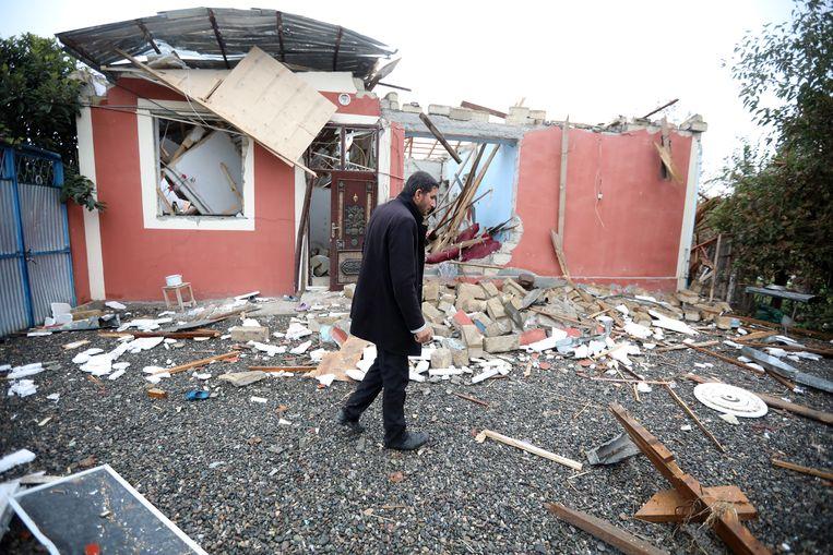 Een man meet de schade op: zijn huis is totaal in puin nadat gewapende troepen van Azerbeidjan en Armenië een oorlog uitvochten over het gebied Nagorno-Karabach.  Beeld EPA