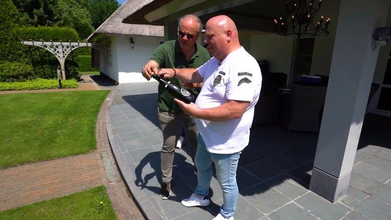 Floris Wyers legt aan Peter Gillis uit hoe je champagne sabreert. Beeld Pure Luxe
