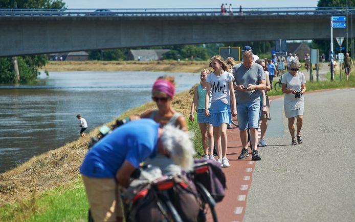 Vanaf de dijk en vanaf de brug bekijken 'ramptoeristen' het hoogwater van de Maas in Ravenstein.