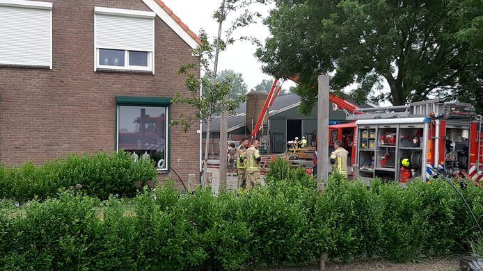 De brandweer probeert te voorkomen dat het vuur overslaat naar de naastgelegen koeienstal (de groene stal op de foto).