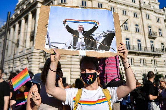 Mensen demonstreren voor het parlementsgebouw in Boedapest tegen de controversiële LGBT-wet in Hongarije. Op het spandoek staat de Hongaarse premier Orban afgebeeld met een regenboogvlag.