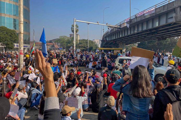 Betogers steken drie vingers in de lucht, een teken van weerstand.