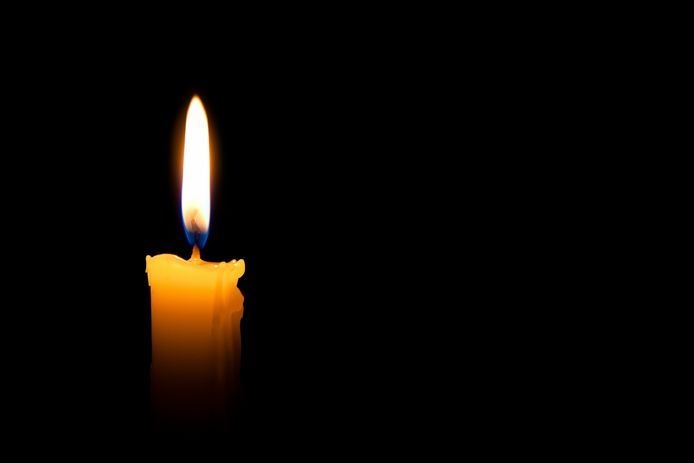 Single lit candle with quite flame on black background - kaars - vlam - lotte - licht - lichtje