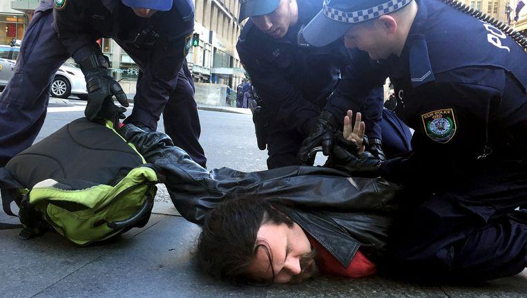 Politieagenten in Sydney houden een man aan na een manifestatie van 'Reclaim Australia'. Beeld REUTERS