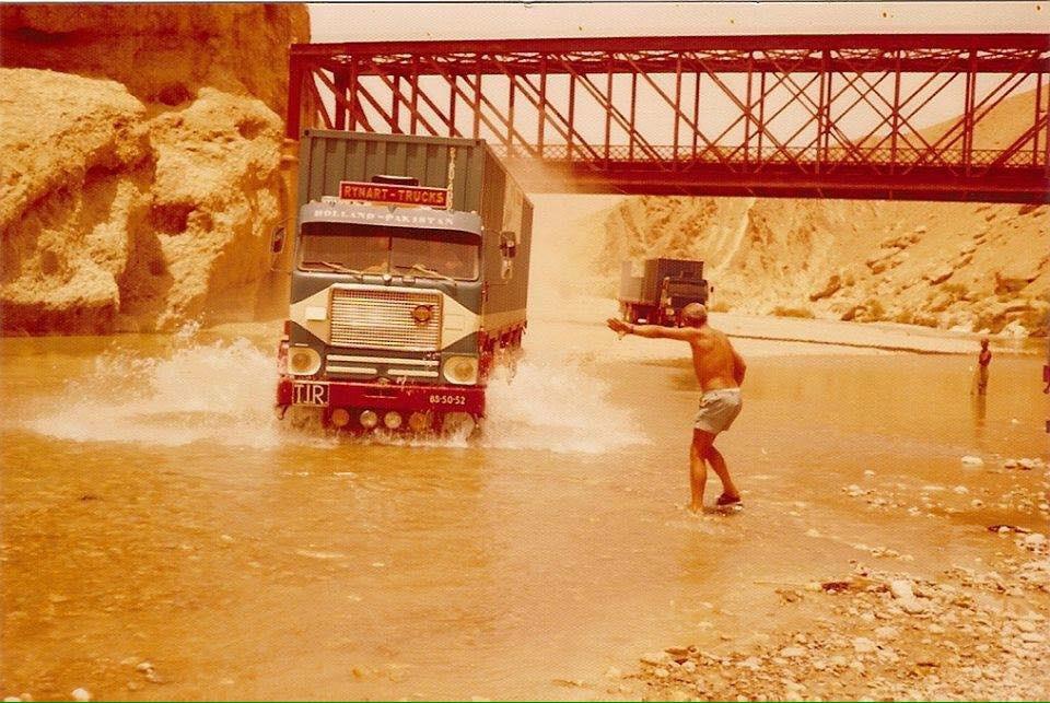Enkele Volvo-trucks van het bedrijf van Rinus Rynart in Pakistan, rond 1975. Ze moeten door een rivier rijden omdat de brug te smal is voor trailers.