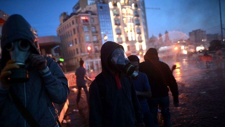 Demonstranten op het Taksim dragen gasmaskers tegen het traangas. Beeld afp