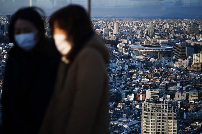Het nieuwe olympisch stadion van Tokio met op de voorgrond twee mensen met een mondkapje.