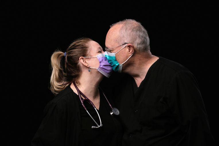 Jozette Dansk and David Dansk, twee Amerikaanse IC-artsen, geven elkaar een kus in coronatijd.  Beeld REUTERS