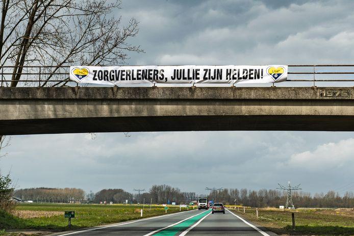 Winssen/Nederland: viaduct Betenlaan over de Maas en Waalweg: Spandoek van UHC.