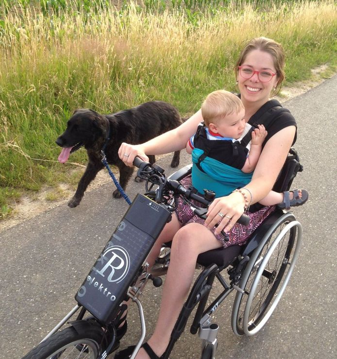 Kim Moorman met zoontje Kick (2) in haar rolstoel, die ze aandrijft met de elektrische handbike die nu gestolen is. Naast haar hulphond Nina (7).