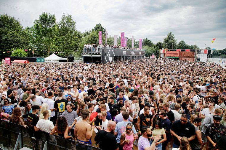 Bezoekers drommen begin juli in Utrecht samen rond het grote podium op het technofestival Verknipt. Van de ruim 20 duizend bezoekers van het tweedaagse festival testten er naderhand 1.100 positief op het coronavirus.  Beeld Foto Ruud Voest