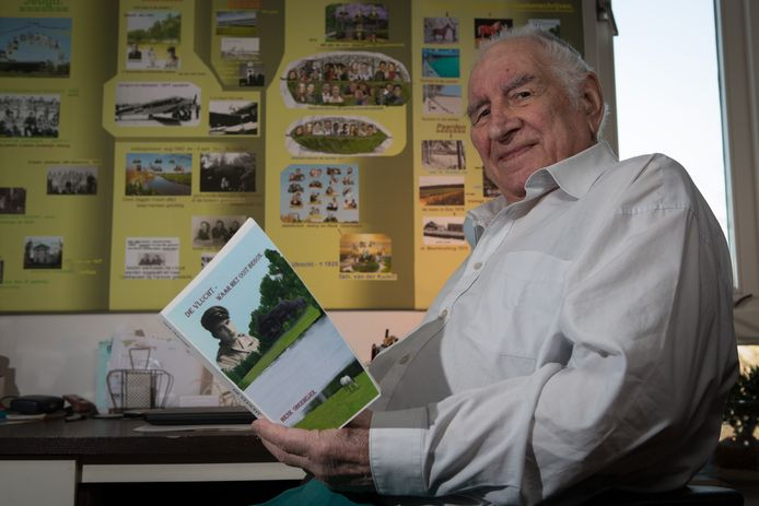Henk Obermeijer met zijn boek 'De Vlucht' voor een bord waarop hij zijn levensloop in kaart heeft gebracht.
