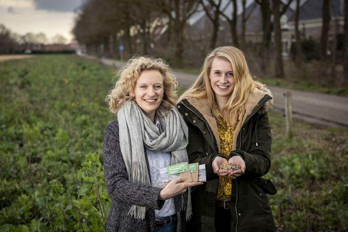 Twee van de drie zussen Renee (links) en Fraukje Roeleveld op een stuk grond langs de Gildehausweg in Denekamp, dat ze eerder inzaaiden met mengsels van wilde bloemen en kruidenplantjes.