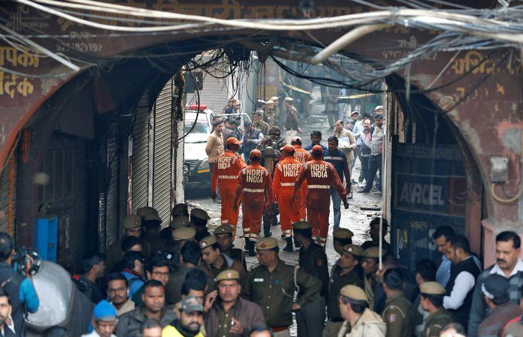 Ambulances zijn ter plekke terwijl politie en brandweer aan het werk zijn bij een brand in fabriek in New Delhi, waarbij tenminste 40 arbeiders omkwamen.  Beeld REUTERS