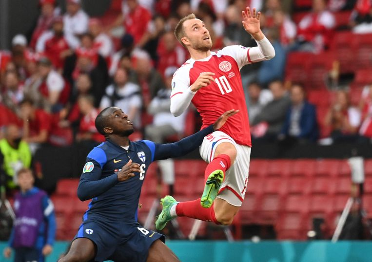 De Deense middenvelder Christian Eriksen springt hoog in een duel met Finland-speler Glen Kamara. Even later zou Eriksen neervallen door een hartfalen. Beeld AFP