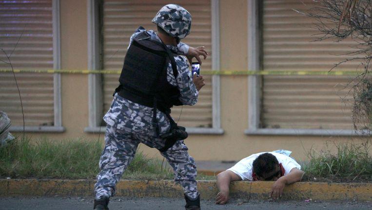 Een politieman maakt een foto van een man die werd doodgeschoten tijdens plunderingen in Veracruz Beeld ap