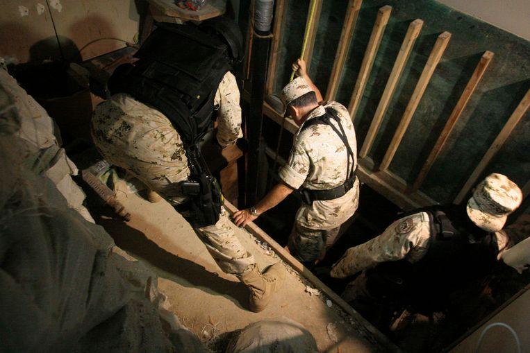 Soldaten inspecteren de ingang van een tunnel die werd aangetroffen in een warenhuis in Tijuana in juli 2012. Beeld REUTERS