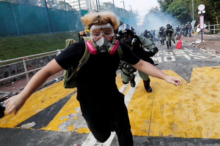 November 2019: een student rent weg voor de oproerpolitie bij de Universiteit van Hongkong. Beeld Reuters