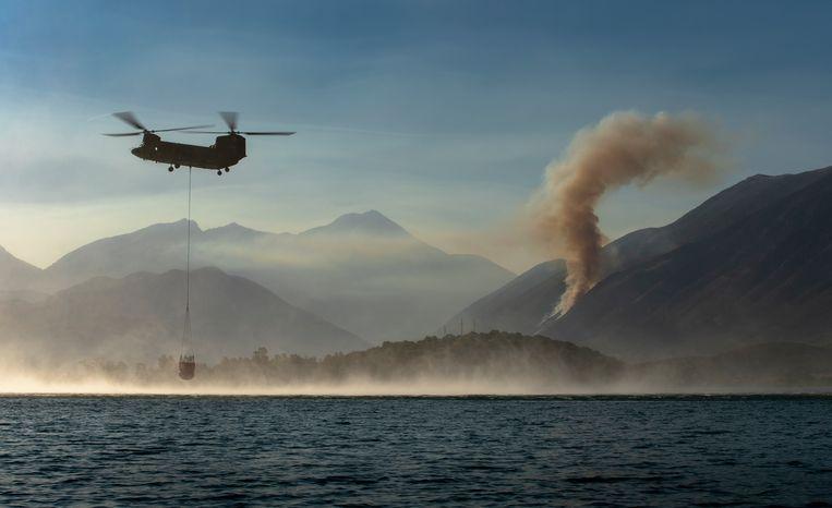 Water uit de Golf van Vlorë wordt over de vlammen op het Albanese schiereiland Karaburun uitgestort. Beeld Hille Hillinga