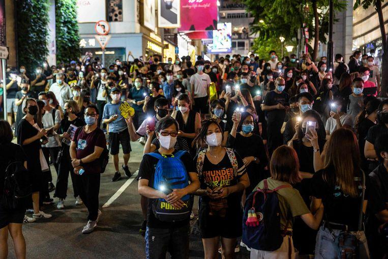Mensen schijnen met hun telefoon, buiten het afgesloten Victoria Park in Hongkong.  Beeld AFP