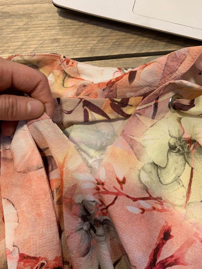 De beschadigde kledij, met scheur aan de V-hals.