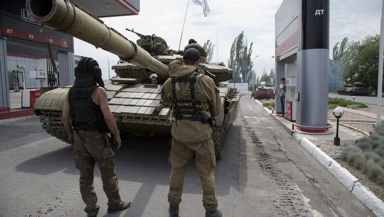 Separatisten vullen de brandstof aan van een tank in Snizhne, 100 kilometer van Donetsk. Beeld AP