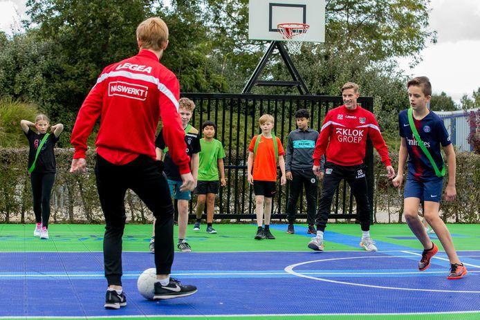 Opening sportcourt bij het PAX Christi College in Druten. Bij de opening waren twee NEC-spelers aanwezig, op de rug gezien met de bal Thomas Beekman en rechts Joep van der Sluijs.