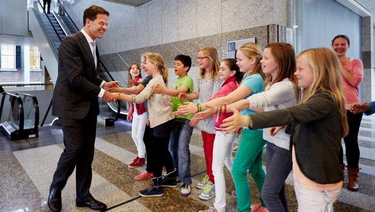 Premier Mark Rutte begroet scholieren van een basisschool uit Oegstgeest voorafgaand aan het verantwoordingsdebat in de Tweede Kamer. Beeld anp