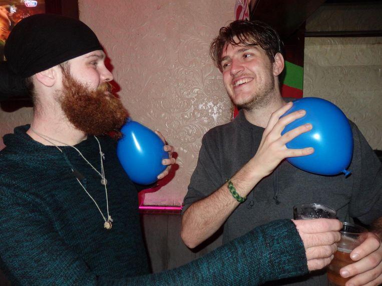 De studenten Sander Horikx (l) en Bryndan van Pinxteren wrijven met ballonnen over hun trui. 'Om een slachtoffer te zoeken.' Pardon? 'Iemands kapsel verpesten' Beeld Schuim