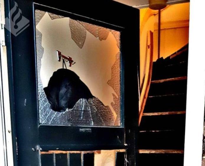 De beschadigde deur van de woning op de Geitenkamp in Arnhem na de inval door een team van de Dienst Speciale Interventies donderdagochtend.