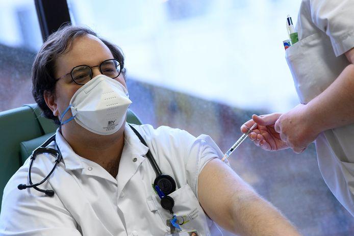 Een UZ Brussel-medewerker wordt ingeënt met het coronavaccin.