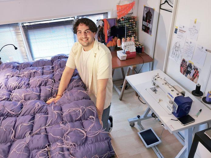 Olivier D'hauwe in de werkkamer van zijn huis in Philippine. Op zijn werktafel ligt een lange, mouwloze jas uit zijn afstudeerproject.