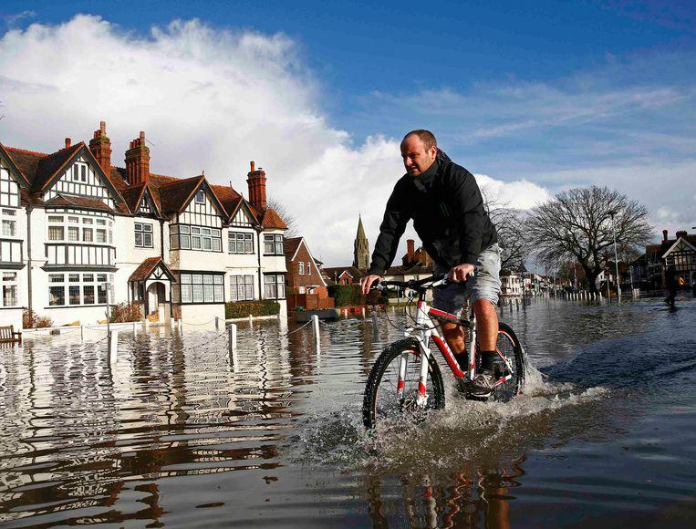 Een inwoner van Datchet.<br /><br />De Engelse overheid waarschuwt voor ernstig overstromingsgevaar in 14 plaatsen langs de de rivier de Theems. Duizenden huishoudens moeten zich daar op voorbereiden. Sinds december zijn al zo'n 8000 woningen getroffen door het hoge water.<br /><br />Ondanks alle maatregelen is vanmiddag het dorp Datchet ook ondergelopen.<br /><br />Na twee maanden van recordneerslag voorspellen meteorologen nog zeker tot en met donderdag iedere dag regen. Vooral de graafschappen Berkshire en Surrey zullen vermoedelijk met wateroverlast te maken krijgen. <br /><br />De Britten worstelen met het natste weer sinds 1766. Het water in de rivier stond in tientallen jaren niet zo hoog en stijgt nog steeds. Beeld REUTERS