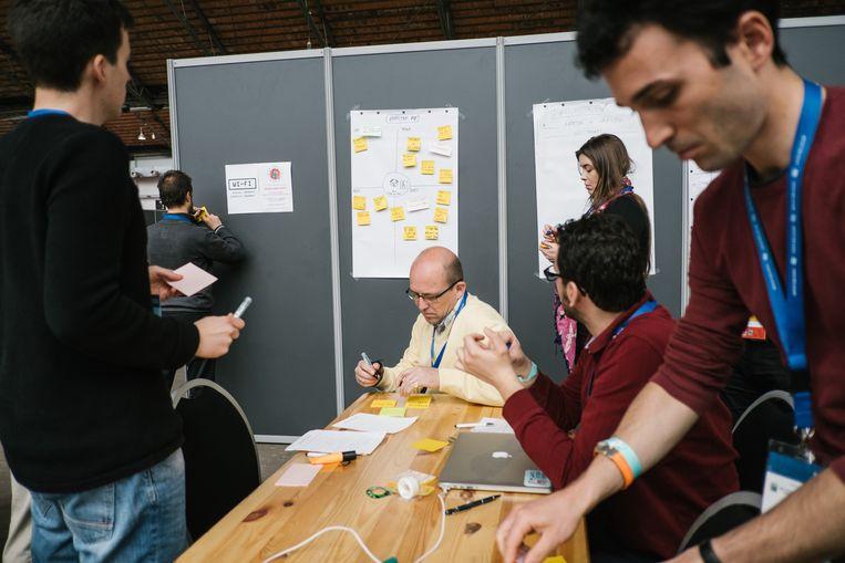 Aan white boards en post-its geen gebrek tijdens de brainstorms op Hack Belgium. Beeld Wouter Van Vooren