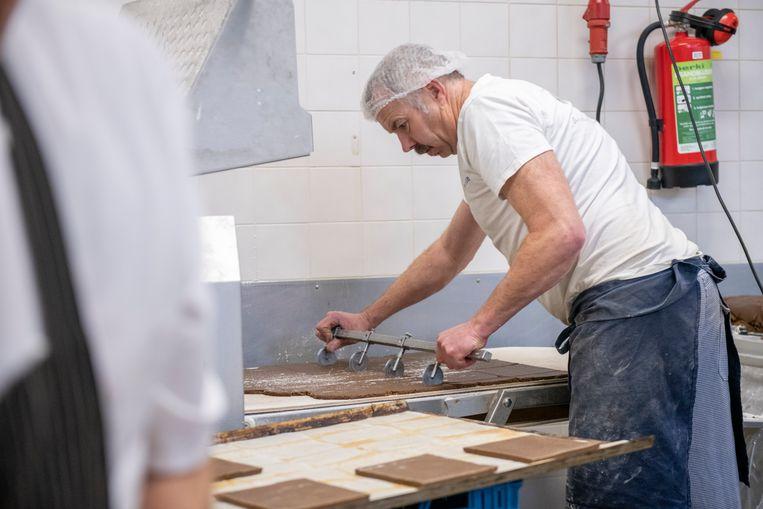 Een medewerker aan het werk in een bakkerij waar producten voor Sinterklaas worden gemaakt. Beeld Hollandse Hoogte / Patricia Rehe
