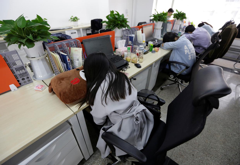Werknemers van het Chinese fintech-bedrijf Goopal in Beijing doen een dutje na de lunch. Beeld Jason Lee / Reuters