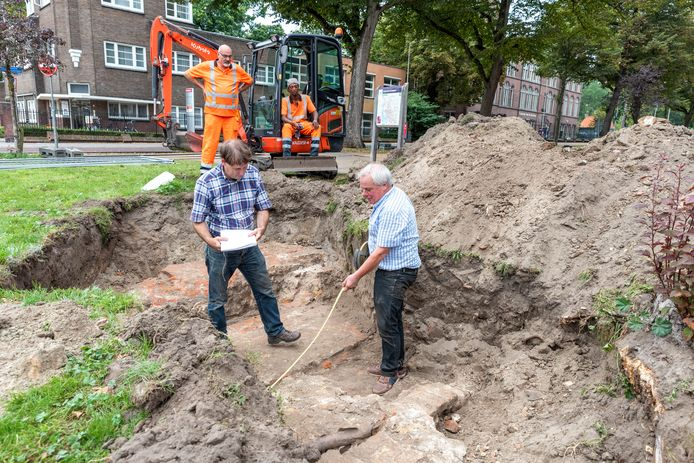Marco Vermunt (l ) en Stefan Asselbergs leggen zoveel mogelijk bloot van de middeleeuwse stadspoort. De werklui op de achtergrond stuitten op de archeologische vondst bij het graven.