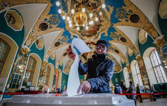 Een man brengt zijn stem uit bij een stembureau in het Kazansky treinstation in Moskou.