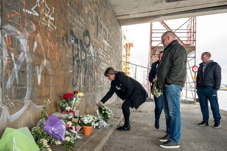 Mensen leggen bloemen neer onder de brug in Merksem, waar Julie Van Espen werd vermoord. Beeld Photo News