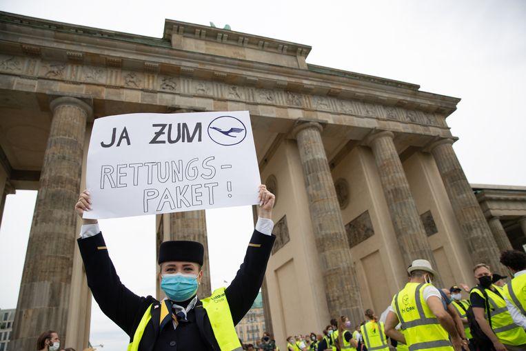 Een werknemer van Lufthansa demonstreert in Berlijn. 'Ja aan het reddingspakket' staat er op het bord geschreven.