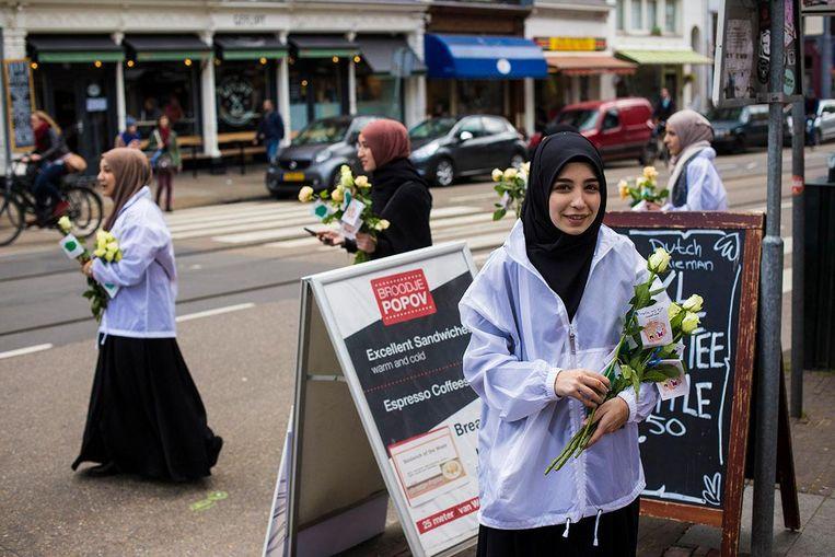 De 16-jarige vwo-scholiere Amine Yildirimtepe deelt rozen uit bij de Van Woustraat. Beeld Maarten Brante