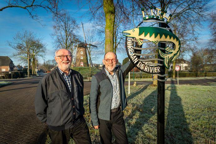 Noud Bongers (rechts)en Mathieu Raemaekers (links) bij het begin van het dorp Lith waar het bord met de snoek staat. Op de achtergrond de molen.