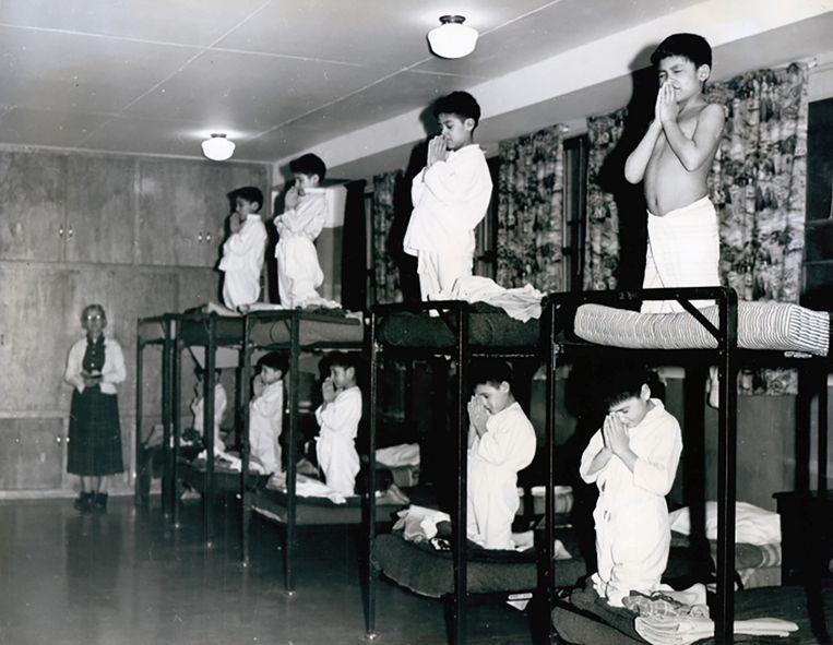 Biddende jongens in de Bishop Horden Memorial School in Moose Factory, Ontario, 1950.  Beeld via REUTERS